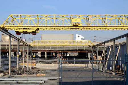 Trucks pass on the freeway next to some cranes in the yard of an industrial unit. Stock Photo