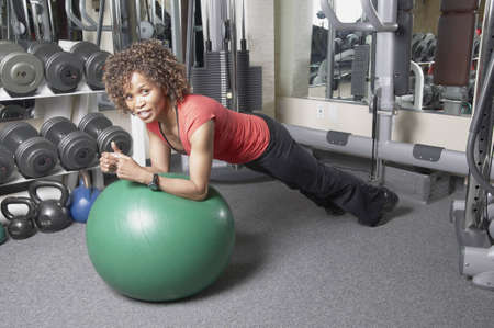 Fit American American woman holding a plank position on a large gym ball  Stock Photo