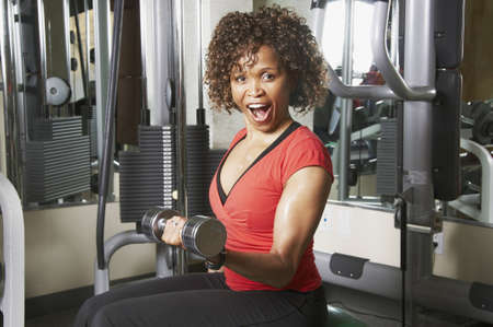 African American woman doing bicep curls in a gym photo