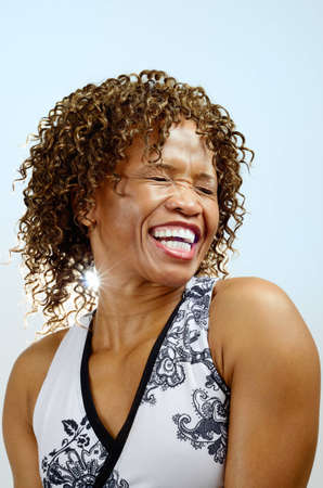 Head and shoulders of a woman laughing with her eyes closed