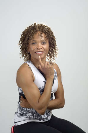 African American woman with loose curly hair sitting and showing her strong arms