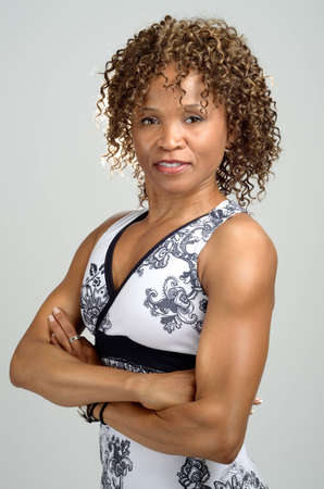 Upper body shot of a fit, toned woman wearing a halter neck sports top