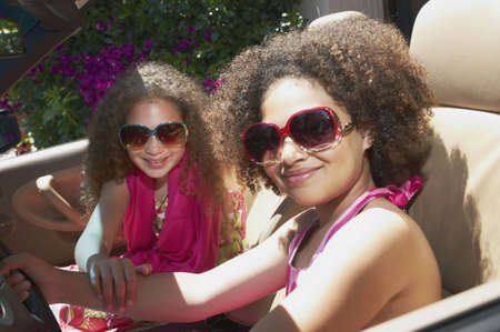 A pair of mixed race young girls wearing sunglasses sitting inside a car