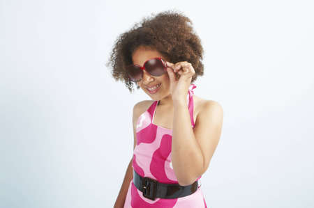 A mixed race girl standing with her sunglasses on Stock Photo