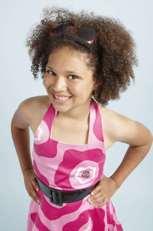 A mixed race girl standing with her hands on her hips and sunglasses in her hair Stock Photo
