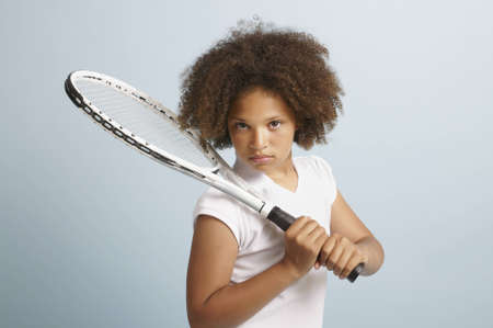 Mixed race young girl with a tennis racket