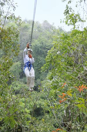 Woman rides a zip line above the rainforest canopy Stock Photo