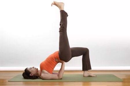 Woman holds an extended bridge yoga pose