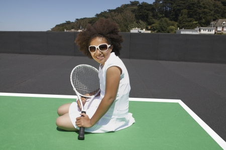 Mixed race girl rests on court with a tennis racket photo