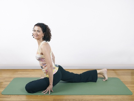 A woman holding a yoga pose on a floormat