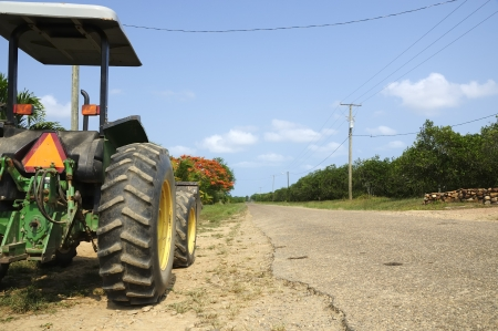 A tractor parked at the side of an empty road viewed from the rear