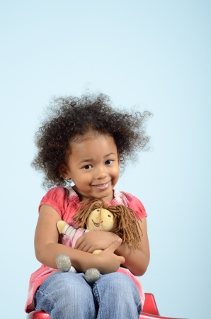 Little girl sitting and hugging a rag doll