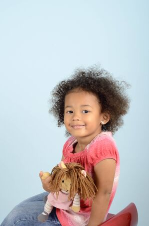 rag doll: Mixed race youg girl with her rag doll