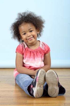 Mixed race girl sitting on the floor