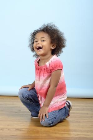 cheerful child kneeling on the floor Stock Photo