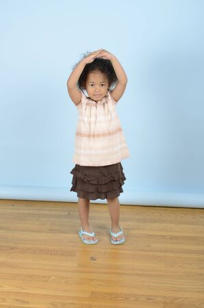 Mixed race little girl with her hands on her head