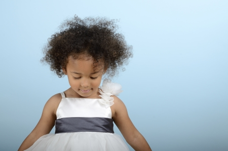 Mixed race girl dressed up and looking down Stock Photo