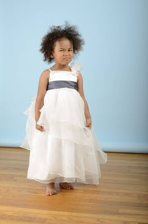 Girl in white dress scowling Stock Photo