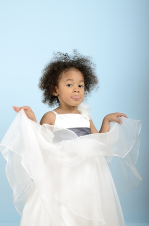 mocking: little girl in her formal dress sticking her tongue out in a mocking way