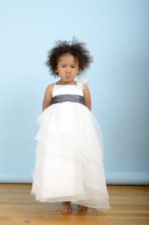 Little girl in a white dress looking unhappy