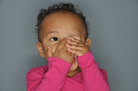 Infant mixed race girl covering one eye with her hands while peeping out of the other eye.