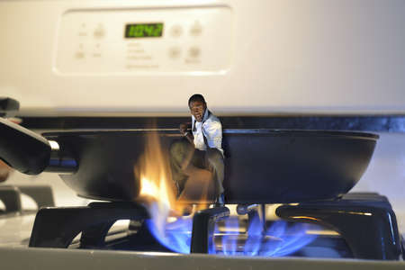 man jumping out of a frying pan and into the fire on a cooker
