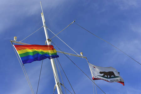 The rainbow banner flies alongside the banner of California Republic on the mast of a yacht