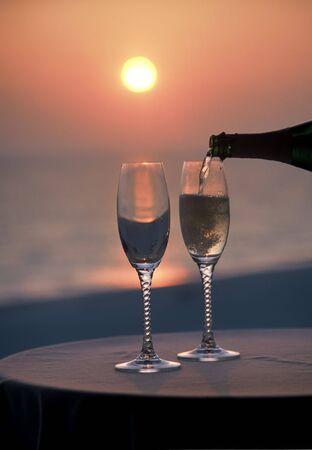 gieten in een glas champagne bij zonsondergang
