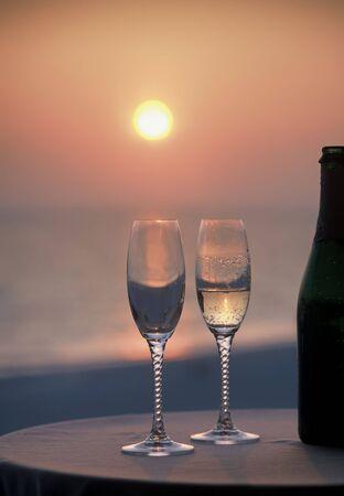 2 glazen 1 volle fles champagne en bij zonsondergang