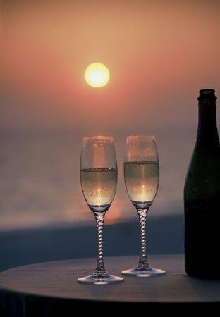 2 glazen champagne en fles bij zonsondergang