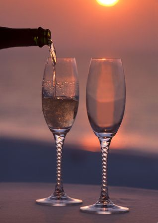 pouring champagne into a glass at sunset