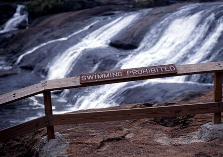 railing with sign with falls in background Standard-Bild