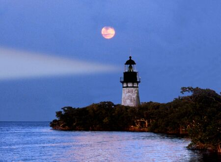 lighthouse on over looking a bay and ocean on a moon lite night