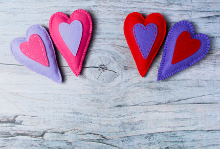 greet card: Hand made felt colorful hearts on wooden background