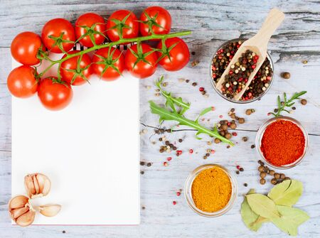 Horizontal food banner with cherry tomatoes, garlic, peppercorns, spice and notebook on wooden background. Empty space for text. Kitchen background. Top view. Concept for flyer, advertise, promotion.