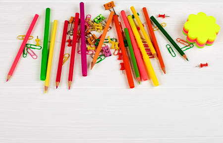 Colorful pencils and felt-tip pens, color notepapers, paper clips, stationery nails on white wooden background. Back to school, chancery, office, stationery horizontal banner. Empty space for text.