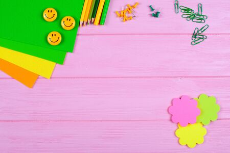 Yellow and green pencils, felt-tip pens, notepaper, paper clips, stationery nails, felt and smiles on pink wooden background. Back to school, chancery, office, horizontal banner. Empty space for text.