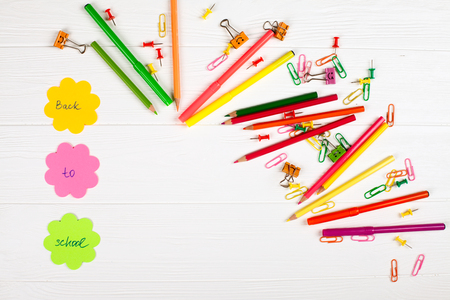 Colorful pencils and felt-tip pens, color notepaper, paper clips, stationery nails on white wooden background. Empty space for text. Back to school, chancery, office, stationery horizontal banner. Stock Photo