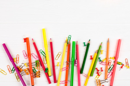 Colorful pencils and felt-tip pens, paper clips, stationery nails, smilie binders on white wooden background. Empty space for text. Back to school, chancery, office, stationery horizontal banner.