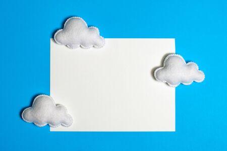Fertigen Sie weiße Wolken im blauen Himmel mit Rahmen, copyspace an. Handgemachte Filzspielzeug. Abstrakter Himmel. Konzept für Reisebüro, Motivation, Geschäftsentwicklung, Grußkarte, Banner, Flyer.