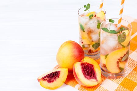 Peach lemonade with ice and mint leaves. Homemade lemonade of ripe nectarine with white and orange ripe. Two glasses of peach tea. Refreshing summer drink. Cocktail on a white wooden background. Stock Photo
