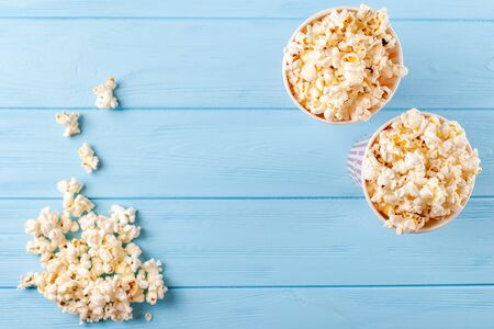 Popcorn horizontal banner. Red stripped paper cup and kernels lying on blue wooden background. Copy space. Top view. For cinema card, flyer, invitation. Stock Photo