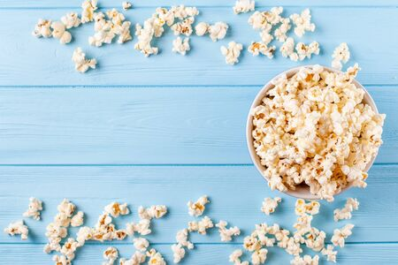 Popcorn horizontal banner. Red stripped paper cup and kernels lying on blue wooden background. Copy space. Top view. For cinema card, flyer, invitation. Stok Fotoğraf