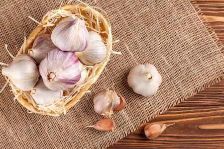 Garlic horizontal banner. Eco farming concept. Whole garlics and cloves in straw basket on piece of sacking on brown wooden textured background. Organic food. Natural spice.