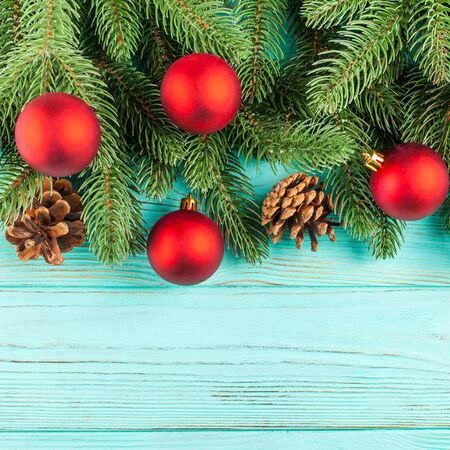 christmas banner with green tree red ball decorations cones on mint wooden textured background