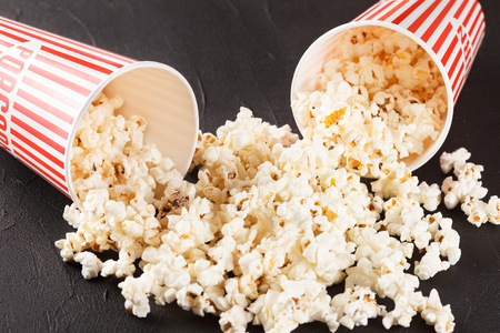 Popcorn horizontal banner. Red stripped paper cup and kernels lying on dark background. Copy space. Top view. For cinema card, flyer, invitation.