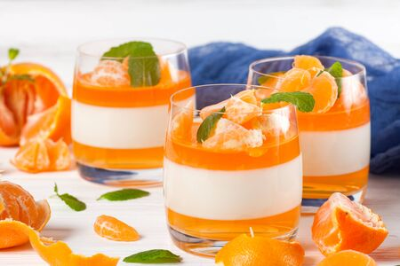 Creamy panna cotta with orange jelly in beautiful glasses, fresh ripe mandarin, blue textile on white wooden background. Delicious Italian dessert.Closeup photography.Selective focus.Horizontal banner