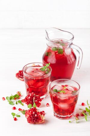 Pomegranate cocktail with ice and mint in beautiful glasses and jug, fresh ripe pomegranate on white wooden background. Sweet red juice. Close up photography. Selective focus. Vertical banner. Stock Photo
