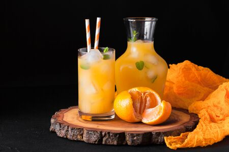 Mandarin cocktail with ice and mint in beautiful glasses and jug, fresh ripe citrus on black background. Dark mood. Sweet orange juice. Close up photography. Selective focus. Horizontal banner. Stock Photo