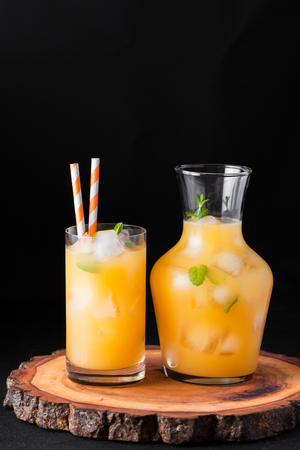 Mandarin cocktail with ice and mint in beautiful glasses and jug, fresh ripe citrus on black background. Dark mood. Sweet orange juice. Close up photography. Selective focus. Vertical banner.